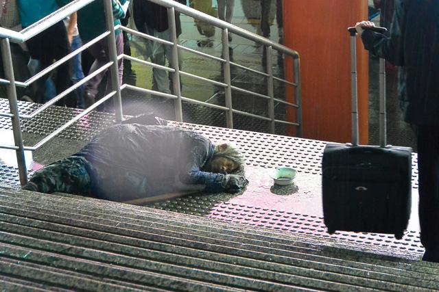 雨に打たれる物乞い@上海人民広場